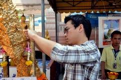 Nakhon Pathom, Thailand: Man Applying Gold Leaf to Buddha Stock Photography