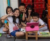 NAKHON SAWAN THAILAND-FEBRUARY 10: en grupp av lyckliga oidentifierade thailändska barn som sitter på lekplatsen med leende på Arkivfoto