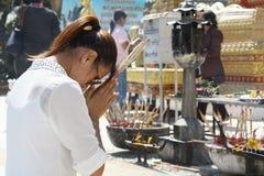 NAKHONPRANOM, TAILÂNDIA - 23 de fevereiro: Na homenagem asiática do pagamento da mulher do templo budista de PhraThatPhanom a uma Imagem de Stock