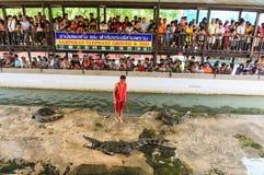 NAKHONPRATOM-PROVINZ THAILAND-APRIL, 4: Reisender sehen Krokodil s Lizenzfreies Stockbild