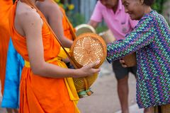 Nakhonsawan,Thailand – October 12: Every day very early in the. Morning, the monks walk the streets to beg give food offerings to a Buddhist monk Stock Photo