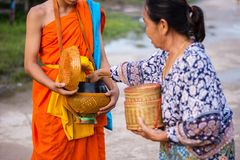 Nakhonsawan,Thailand – October 12: Every day very early in the. Morning, the monks walk the streets to beg give food offerings to a Buddhist monk Stock Photos