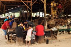 NAKHONSITHAMMARAT, THAILAND - JUNE 7, 2014: Big family on private brick factory, Group of adults and children under huge cover of. Private family brick factory royalty free stock image