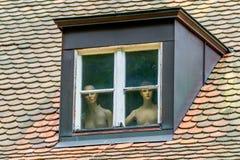 Nakna kvinnor bak ett fönster Arkivbild