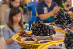 NAKORNPATHOM, THAILAND - JUL 5, 2014 : Grapes and many black thi Stock Photography