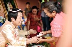 NAKORNRACHASIMA THAILAND - JULI: Oidentifierade par i bröllopceremoni på Juli 21,2013 i Nakornrachasima, Thailand. Välsignad wate Royaltyfri Bild