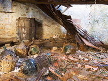 Nalatigheid, bouwvallig verlaten bezit, kelder met korfflessen royalty-vrije stock afbeeldingen