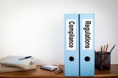Naleving en Verordeningen bindmiddelen in het bureau Kantoorbehoeften op een houten plank Royalty-vrije Stock Afbeeldingen