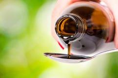 Nalewać ciecz na łyżce zielony środowisk naturalnych Apteka i zdrowy tło Medycyna Kasłanie i zimny lek obraz stock