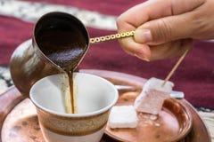 Nalewać czarną kawę w filiżance Zdjęcia Royalty Free