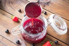 Nalewać domowej roboty jagodowego dżem w słój Zdjęcia Stock