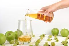 Nalewać jabłczanego sok w szkło Obrazy Stock