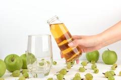 Nalewać jabłczanego sok w szkło Zdjęcie Stock