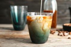 Nalewać mleko w szkło z zimną parzenie kawą obraz royalty free