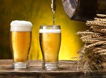 Nalewać w piwnego szkło Szkła piwo i beczka na drewnianym stole zdjęcia royalty free
