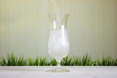 Nalewać wodę na szkle na jaskrawym tle Zdjęcie Royalty Free