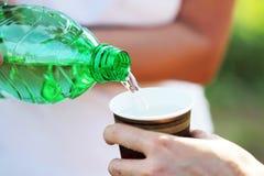 Nalewać wodę od zielonej butelki Zdjęcie Royalty Free