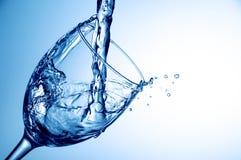 Nalewać wodę w szkło na błękitnym tle, zakończenie Fotografia Stock