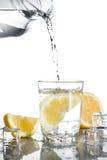 Nalewać wodę w szkło z cytrynami i lodem Zdjęcia Royalty Free