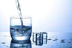 Nalewać wodny od szklanych pobliskich kostek lodu z pluśnięciami w Obraz Stock