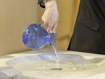 Nalewać Wodny w Chrzcielną chrzcielnicę Zdjęcie Stock