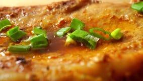 Nalewać zieloną cebulę na piec mięsnym makro- dolly strzale zdjęcie wideo