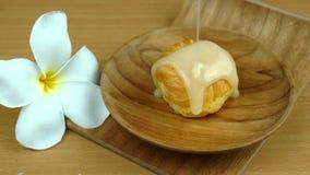 Nalewa cukierki kondensującego mleko na aclair w drewnianym talerzu na drewnianej tacy zbiory wideo