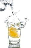 Nalewa wodę w szkle z cytryną Zdjęcia Stock