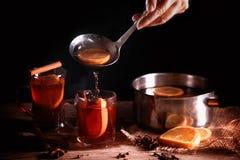 Nalewający gorącego rozmyślającego wino od garnka w szklanych kubkach i wewnątrz, Christm obrazy stock