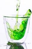 Nalewający zieleni wodę wewnątrz rozjaśniać szkło Fotografia Stock