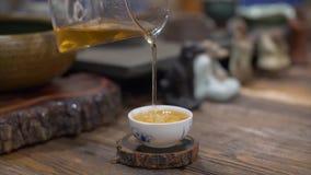 Nalewam warzył zielonej herbaty w białej ceramicznej filiżance od szklanego teapot zwolnionego tempa zbiory
