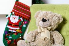 Nallebjörn i en stol under julgranen Royaltyfri Bild