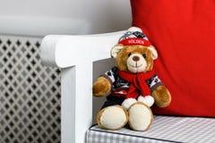 Nallebjörn i en stol under julgranen Arkivfoto