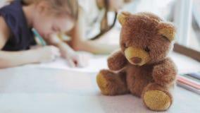 Nallebjörn i närbilden, två flickaattraktionbilder på suddig bakgrund arkivfilmer