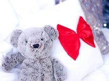 Nallebjörn i säng nära julgranen royaltyfria foton