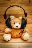 Nallebjörn med hörlurar Arkivbild
