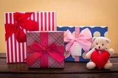 Nallebjörn med rosa hjärtagarnering på ros- och gåvagåvanolla Arkivfoto