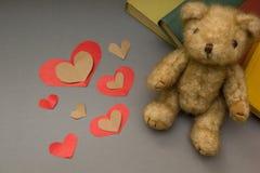 Nallebjörn på en grå bakgrund, en röd hjärta royaltyfri bild