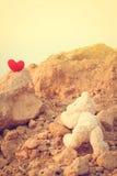 Nallebjörn som klättrar en röd hjärta med målen royaltyfri bild