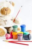 Nallebjörn som målar tecknet av den lyckliga ungen på att lära Arkivbild