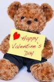 Nallebjörn som rymmer ett gult tecken som säger lycklig dag för valentin` s Fotografering för Bildbyråer