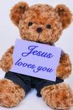 Nallebjörn som rymmer ett purpurfärgat tecken som säger Jesus förälskelser dig royaltyfri foto