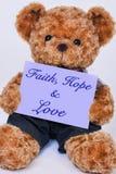 Nallebjörn som rymmer ett purpurfärgat tecken som säger tro, hopp och förälskelse fotografering för bildbyråer