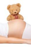 Nallebjörn som ser buken av en gravid kvinna royaltyfria foton