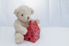 Nallebjörn som sitter med det röda huset på vitt tyg arkivbild