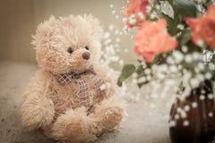 Nallebjörn som sitter nära en bukett av rosor royaltyfri bild