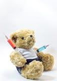Nallebjörnen som bär plast- läkarundersökning, spolar ren innehålla färgrika flytande Royaltyfria Bilder