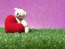 Nallebjörnen som rymmer en handgjord röd hjärta på bakgrund för grönt gräs, är den kungliga rosa färgen Kopiera utrymme för text, royaltyfria bilder