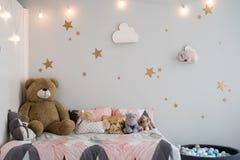 Nallebj?rn mellan pappers- p?sar och tr?stolar i barns rum med den pastellf?rgade lampan ovanf?r tabellen royaltyfria foton