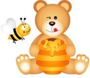Nallebjörnen äter det ilskna honung och biet Arkivbild